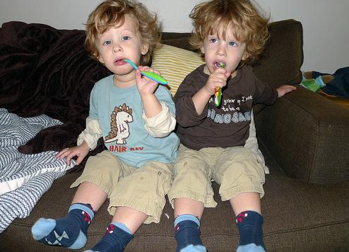 Photo of two young children both working on brushing their teeth by themselves!