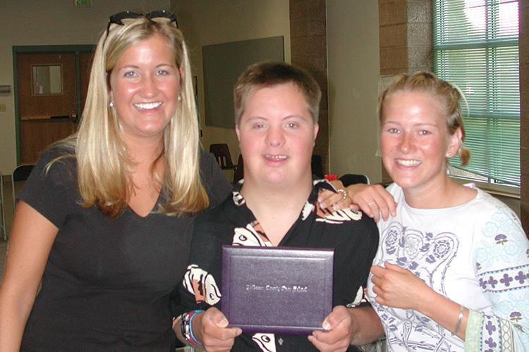 Photo of student with Down syndrome, along with two friends, proudly holding up his high school diploma!