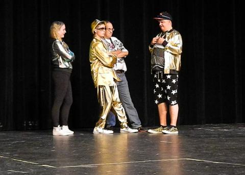 Photo of young people on stage in hip hop gear