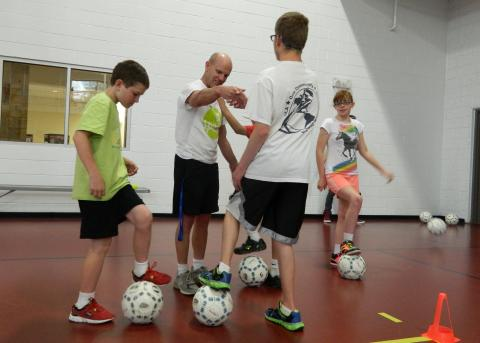 Photo of young people playing indoor soccer