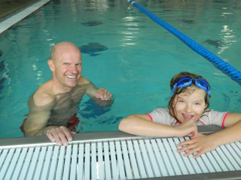 Photo of two people swimming in a pool