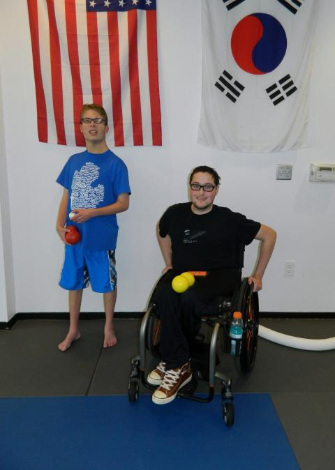 Photo of two individuals preparing to do some fitness, one of whom uses a wheelchair