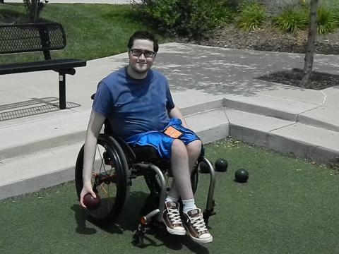 Photo of man who uses wheelchair playing bocci ball
