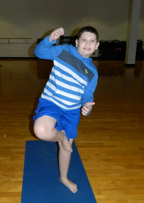 Photo of young boy practicing yoga
