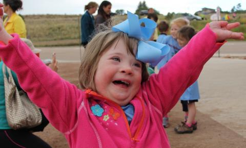 Photo of a young girl with her arms wide open