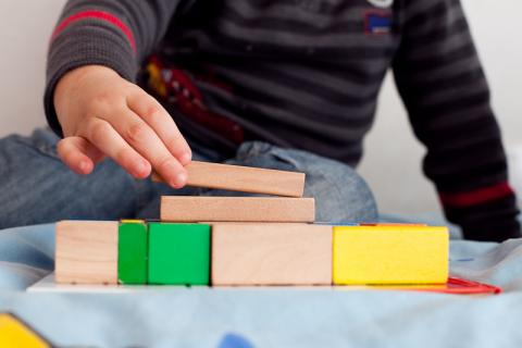 Photo of young child building with wooden building blocks.