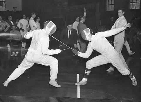 Older, black and white photograph of two people fencing