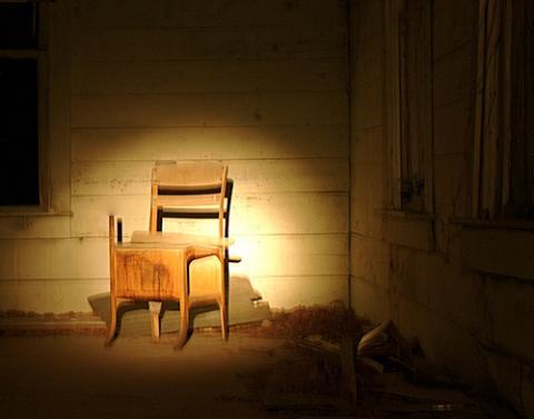 Photo of empty desk in a dark room.