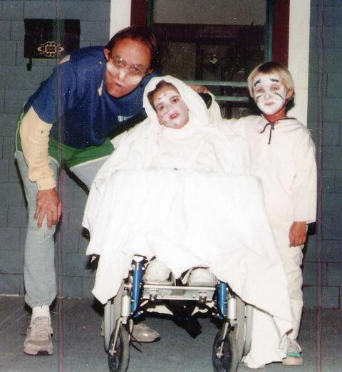 Photo of a Dad with his kids on Halloween, where his kids are dressed as ghosts, and one child uses a wheelchair.