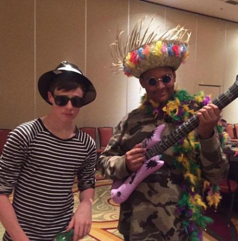 Photo of two young men dressed in fun costumes at a karaoke party