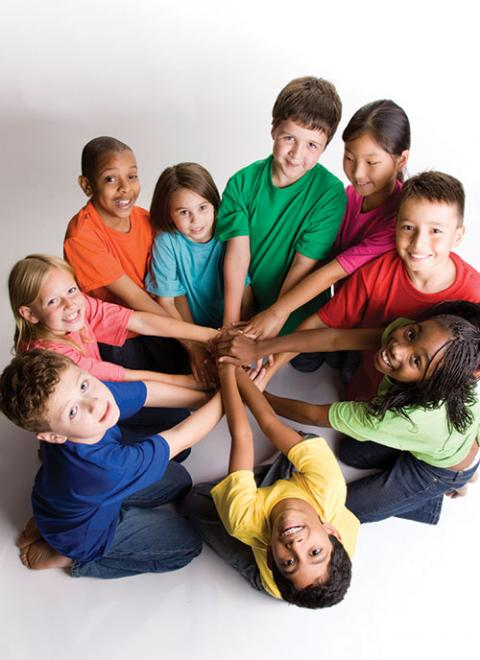 Photo of kids from many backgrounds with their arms in for teamwork!