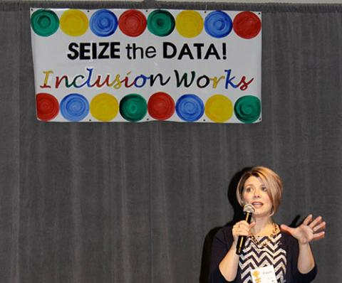 "Photo of Paula Kluth presenting at PEAK's Conference on Inclusive Education in front of a banner that reads ""Seize the Data! Inclusion Works"""