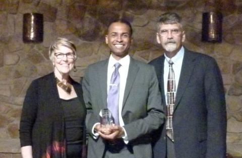 Photo of LeDerick Horne holding his Ally for Inclusion Award with Barb Buswell and Dave Meeks