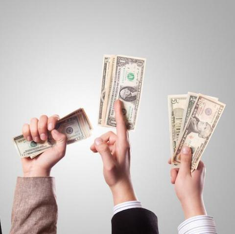 Photo of three people's hands raised holding money