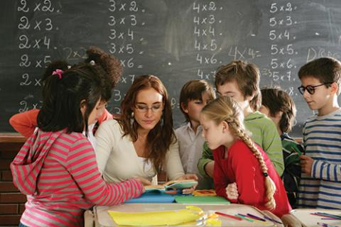Photo of Teacher in Classroom Surrounded by Engaged Students