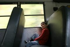Photo of a student sitting alone on a school bus.