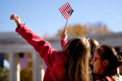 Photo of a young girl being held up in the air at a Veteran's Day rally, waving an American Flag.