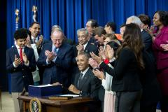 Photo of President Obama smiling, surrounded by students and colleagues, just after signing the new ESSA law.