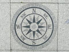 Photo of a compass on a sidewalk.