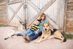 Photo of a mom with her son and two dogs smiling in front of a barn