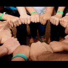 Photo of a group of youth with their hands all in a circle