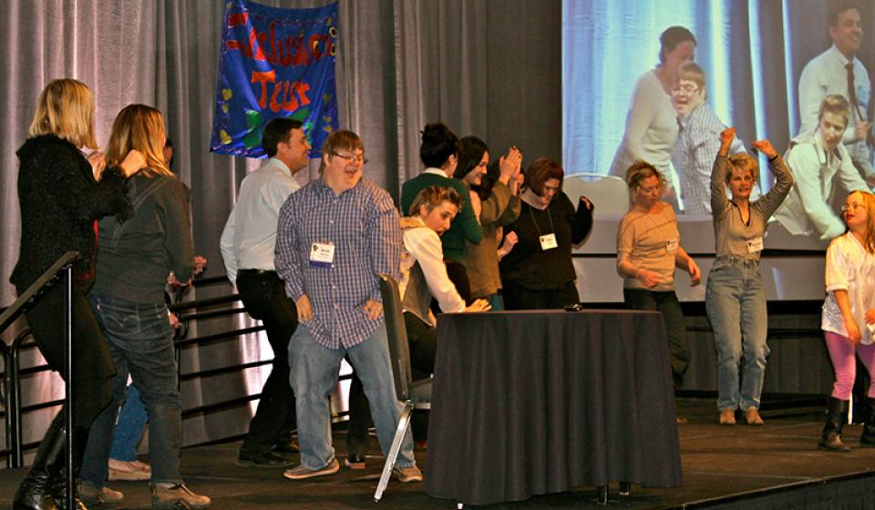 Photo of Participants Dancing on Stage with Keynote Presenter Patrick Schwarz at PEAK's 2014 Conference on Inclusive Education